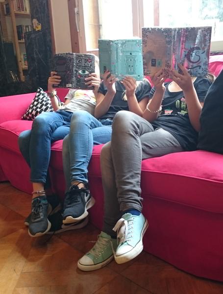 Mehrere Schülerinnen, die ein Buch nebeneinader lesen und dabei das Buch vor ihr Gesicht halten