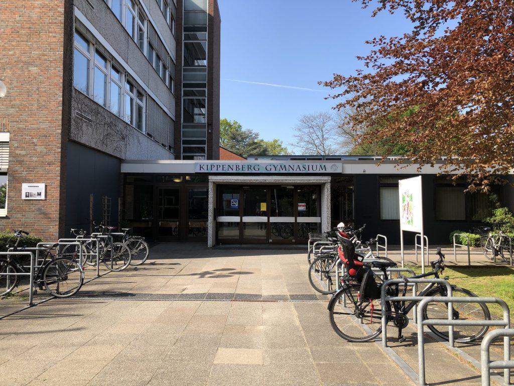 """Frontalansicht des Haupteingangs mit Schriftzug """"Kippenberg-Gymnasium"""" über der Eingangstür"""