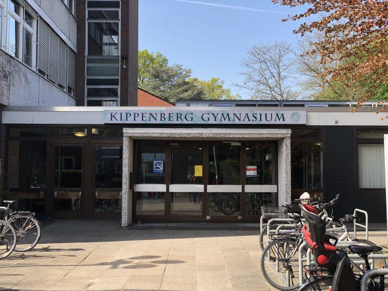"""Nahaufnahme der Frontalansicht des Haupteingangs mit Schriftzug """"Kippenberg-Gymnasium"""" über der Eingangstür"""