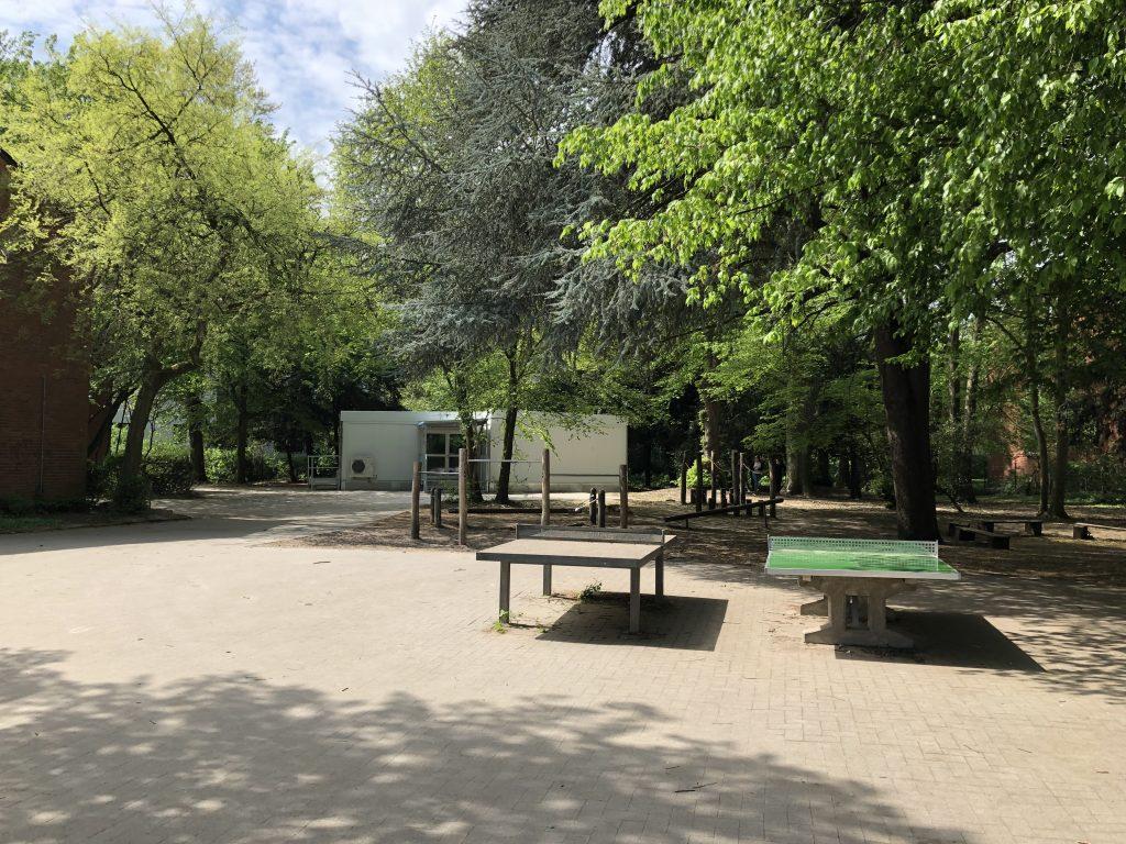 Blick vom Schulhof in Richtung der Tischtennisplatten, des Containers und Haus 2