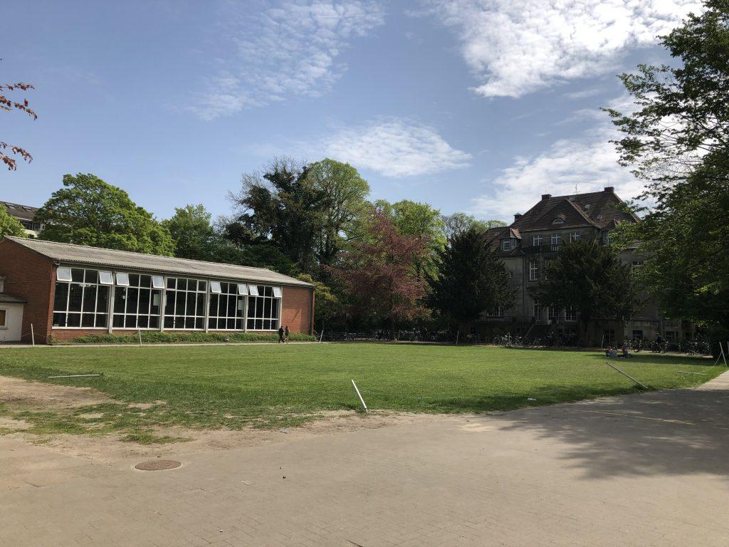 Blick vom Schulhof in Richtung Sportrasen, alter Turnhalle und Vietorhaus