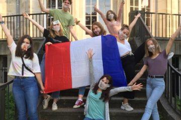 Verschiedene Schüler*innen mit einer Frankreich-Flagge, die ihre arme triumphierend in die Höhe strecken